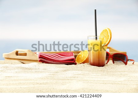 summer beach background of tray of wood and orange juice and sunglasses and sun