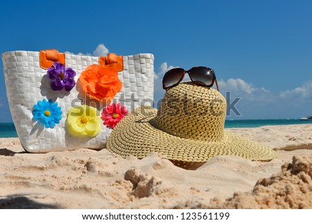 Summer beach bag with straw hat and sunglasses on sandy beach - stock photo