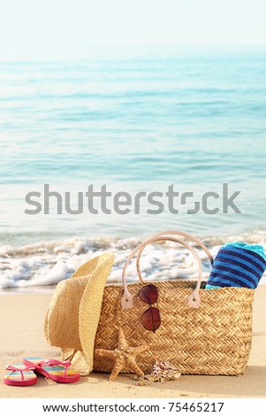 Summer beach bag with straw hat,towel,sunglasses and flip flops on sandy beach - stock photo