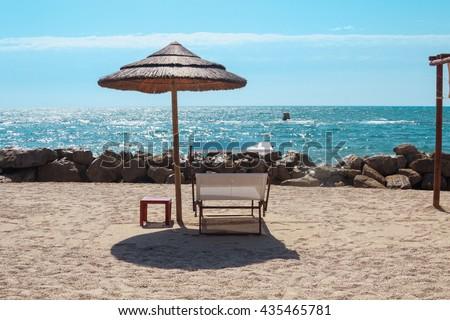 Summer Beach chairs on a sand beach with cloudy blue sky and sun - stock photo