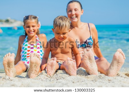 Summer beach - family playing on sandy beach. Focus on the feet