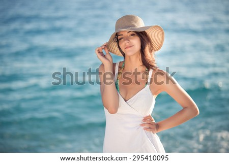Summer beach fashion woman enjoying summer and sun,walking the beach near clear blue sea,smiling at camera.Concept of summer feeling,freedom,happiness.Fit and healthy summer body - stock photo