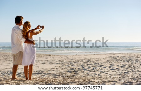 Summer beach honeymoon couple standing on the sand and taking pictures of the beautiful sunset over the ocean - stock photo