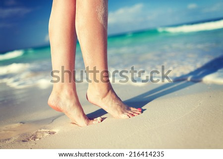summer, beach, leisure and body part concept - closeup of woman legs on sea shore - stock photo