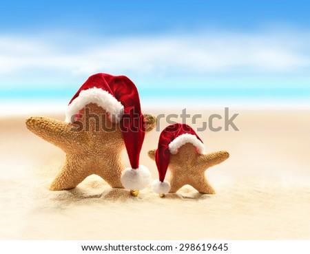 Summer beach. Merry Christmas. Starfish in Santa Claus hat. - stock photo