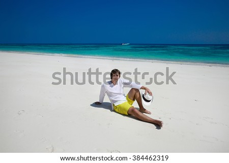 Summer beach. Relax. Successful handsome man in hat resting on exotic seashore with blue water and white sand. Vacation Travel. Bliss freedom concept.  - stock photo