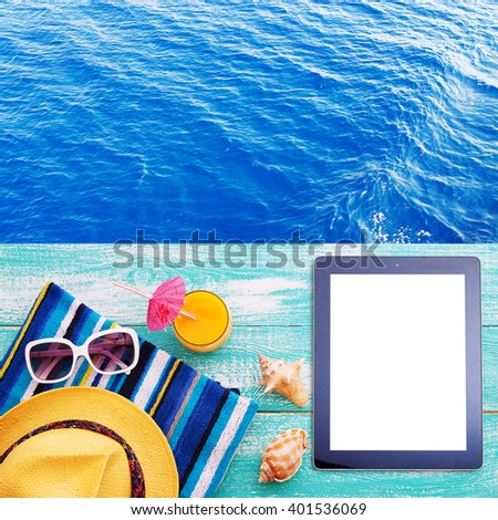 Summer beach, set of summer accessories and tablet. Workplace for freelancer