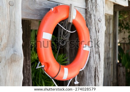 summer, beach, swimming and life saving concept - lifebuoy or life preserver hanging on rescue booth - stock photo