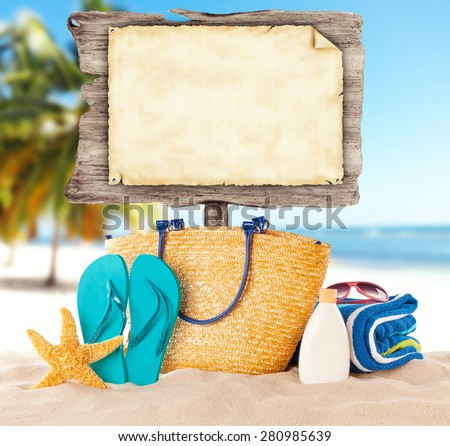 Summer beach with accessories and blank wooden poster. Blur azure sea on background - stock photo