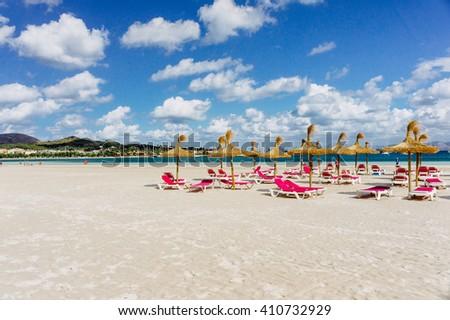 Summer beach with sun umbrellas and sunbeds, Majorca, Spain. Sunny day beach. Pink sunbeds at beach, Majorca. Summer beach paradise. Summer day at a beach. Beauty of Majorca nature. Summer day beach. - stock photo