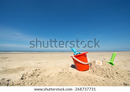 Summer beach with toys and flip flops - stock photo