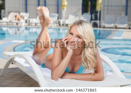Summer beauty. Cheerful young women in bikini lying on the deck chair near the pool and holding her head in hand - stock photo