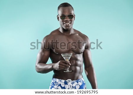 Summer black african american muscled fitness man holding cocktail drink. Wearing blue swimming shorts and sunglasses. Studio shot against blue. - stock photo