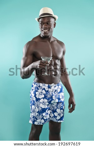 Summer black african american muscled fitness man holding cocktail drink. Wearing blue swimming shorts and hat. Studio shot against blue. - stock photo