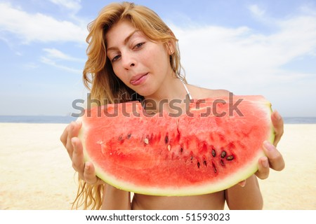 summer: blond woman eating watermelon on the beach