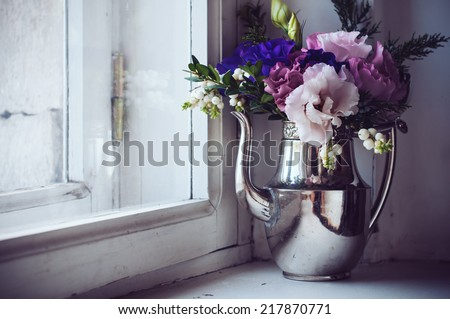 Summer bouquet of purple and pink eustomas in an antique coffee pot on the windowsill, vintage style, holiday home floral decor - stock photo