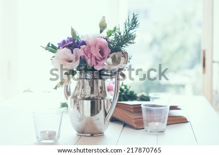 Summer bouquet of purple and pink eustomas in an antique coffee pot on white wooden table, vintage style, holiday and wedding floral decorations - stock photo