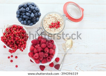 Summer breakfast. Ingredients for healthy breakfast - berries, fruit and muesli on white wooden table, close-up top view horizontal. Macro shot selective focus