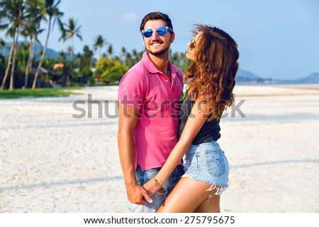 Summer bright fashion portrait of beautiful couple in love, wearing stylish bright casual hipster clothes and sunglasses, holding hands hugs and enjoy their vacation near ocean. - stock photo
