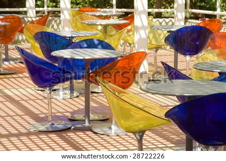 Summer cafe with round little tables and colour transparent plastic chairs