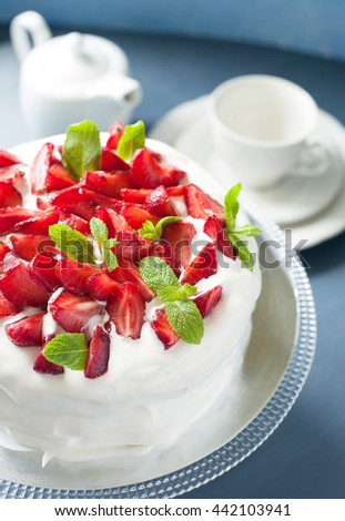 Summer cake with strawberries and mint decorated with whipped cream on stand with tea accessories, close up, vertical - stock photo