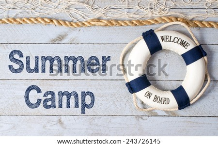 Summer Camp - lifebuoy with fishnet and text on wooden background - stock photo