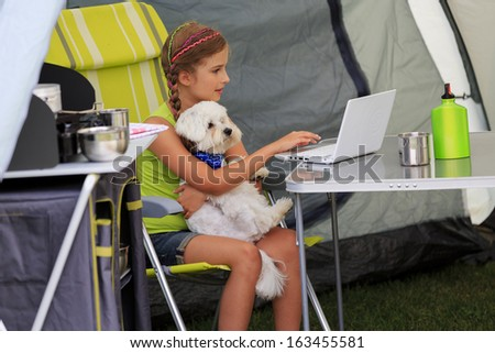 Summer camp - young girl with dog playing in the tent - stock photo