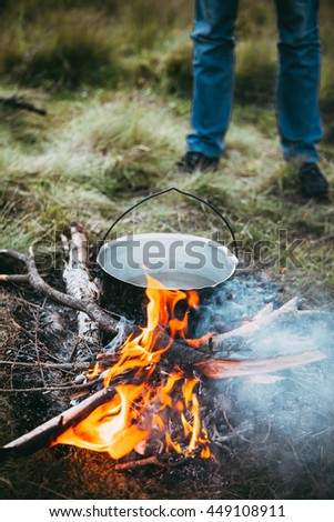Summer camping food cooking on man and landscape background - stock photo