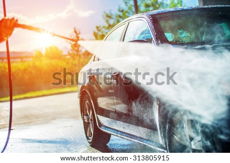 Summer Car Washing. Cleaning Car Using High Pressure Water.  - stock photo