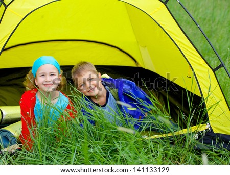 Summer, child camping in tent - lovely sister and brother on camp tent - stock photo