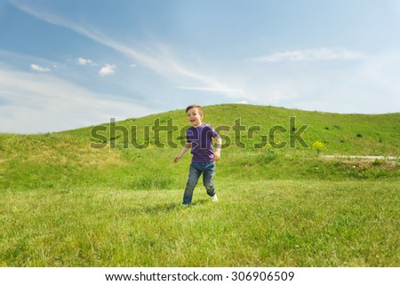 summer, childhood, leisure and people concept - happy little boy running on green field outdoors