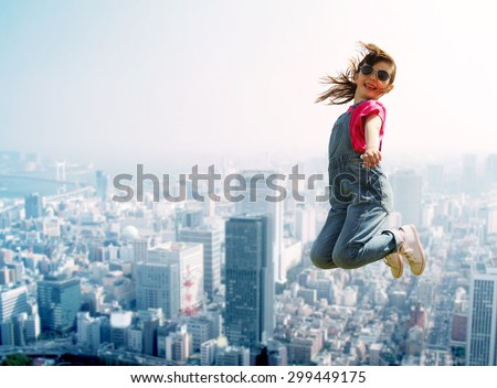 summer, childhood, leisure and people concept - happy little girl jumping high over city background - stock photo