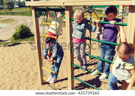 summer, childhood, leisure, friendship and people concept - group of happy kids on children playground climbing frame