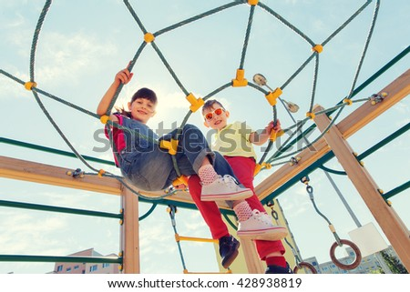 summer, childhood, leisure, friendship and people concept - group of happy kids on children playground climbing frame - stock photo