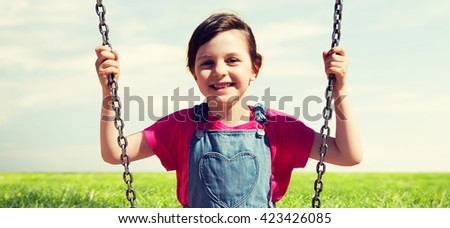 summer, childhood, leisure, friendship and people concept - happy little girl swinging on swing over blue sky and grass background - stock photo