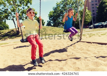 summer, childhood, leisure, friendship and people concept - two happy kids swinging on swing at children playground - stock photo