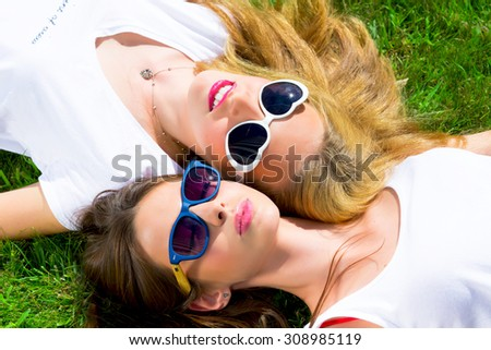 Summer Close up lifestyle fashion portrait of two pretty fresh young brunette and blonde best friends girls,having Europe vacation ,wearing white t-shirts and sunglasses.Positive and young. - stock photo