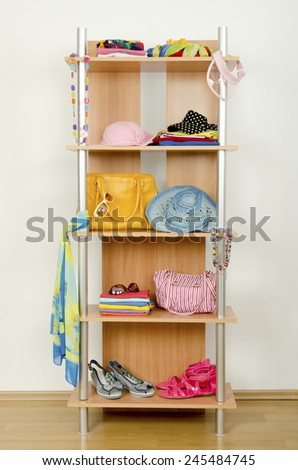 Summer clothes nicely arranged on a shelf. Tidy wardrobe with colorful clothes and accessories.