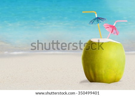 Summer cocktail in fresh green coconut with two colorful umbrellas on beach and ocean background