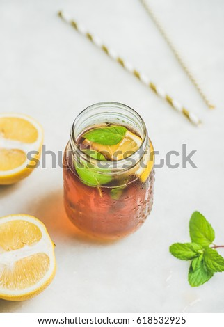 Summer cold Iced tea with fresh bergamot, mint and lemon in glass jar on light table background