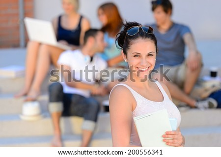Summer college student girl smiling holding books friends in background - stock photo