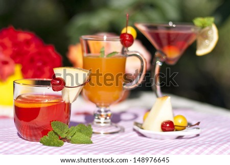 Summer colored cocktails, decorated with lemon, melon, cherry, plum and mint - stock photo