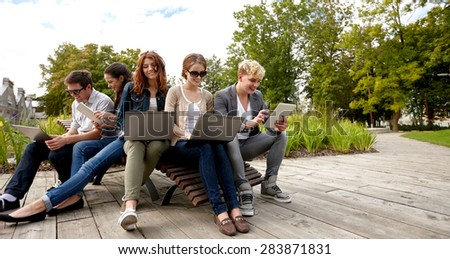 summer, communication, technology , education and teenage concept - group of students or teenagers with laptop and tablet pc computers at park or campus - stock photo