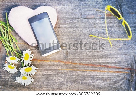 Summer composition with smartphone and chamomile flowers on the wooden background. Toned image - stock photo