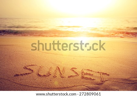Summer concept of beach with word sunset written on the sand - stock photo