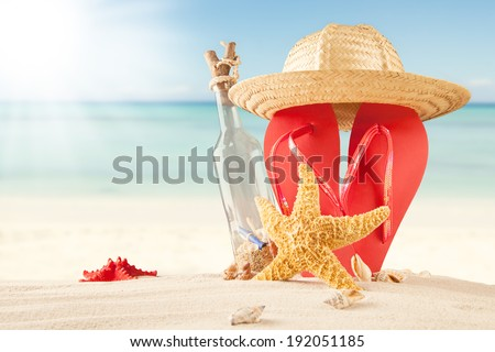 Summer concept of sandy beach, bottle with message, shells and starfish. - stock photo