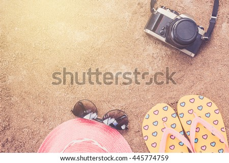 Summer concept with accessories on sand beach,sandals;camera,sunglasses,hat. - stock photo