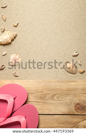 Summer concept with pink flip flops and shells on sandy beach. Top view