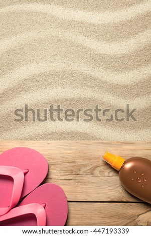 Summer concept with pink flip flops and suntan oil on sandy beach