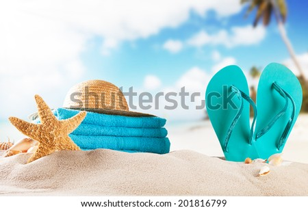 Summer concept with sandy beach, shells and sandals - stock photo